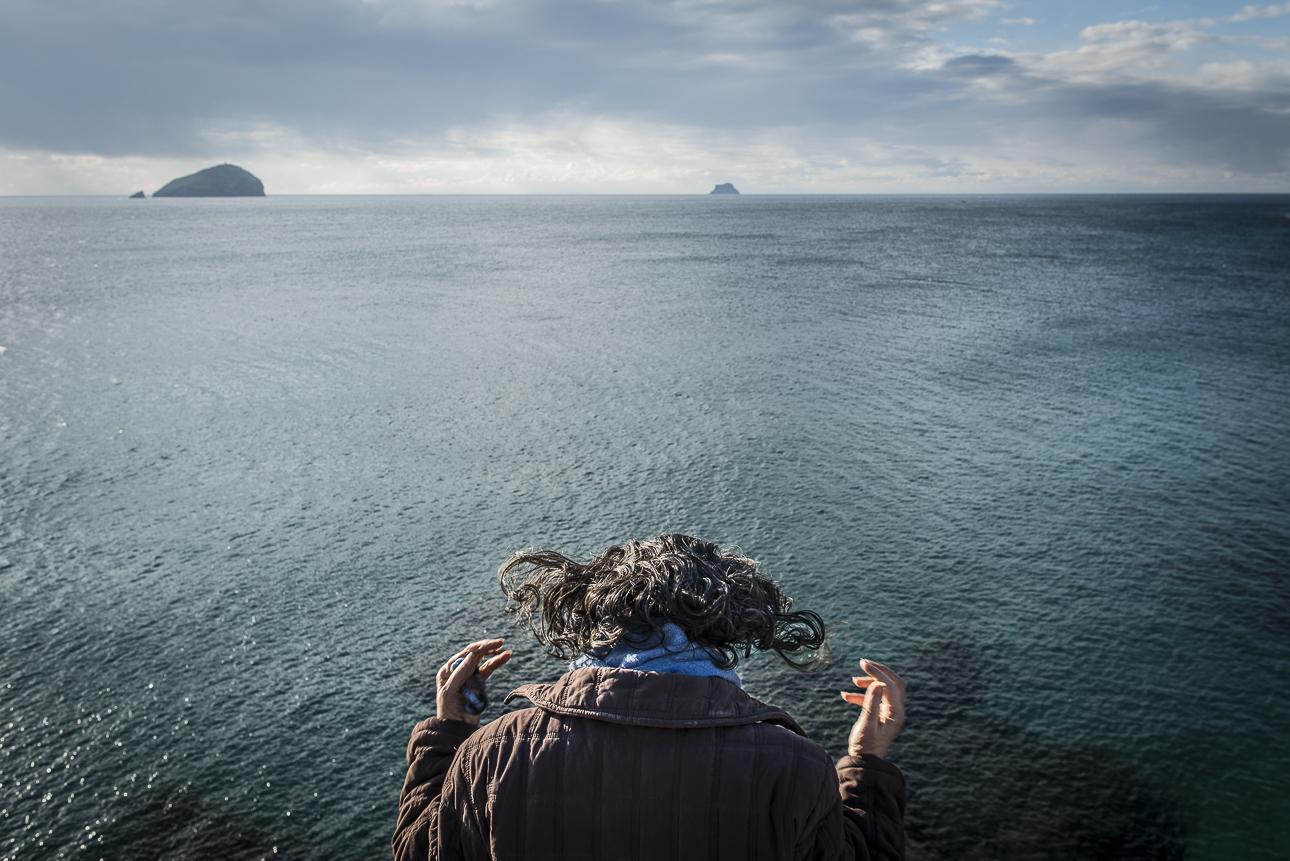 """ITA  Italia, Sardegna, Turri, dicembre 2017.  Chiara prega di fronte al mare. Chiara è l'ultimo Maestro di Bisso marino. È una sacerdotessa dell'acqua. Per ricoprire questo ruolo, che viene tramandato in linea matriarcale nella stessa famiglia, il Maestro è tenuto a rispettare il giuramento dell'acqua: """"Ponente, Levante, Maestrale e Grecale - Prendetevi la mia anima e buttatela nel fondale - che sia la mia vita per essere, pregare e tessere – per ogni gente che da me va e da me viene - senza tempo, senza nome, senza colore, senza confini, senza denaro- nel nome del leone dell'anima mia e dello spirito eterno così sarà"""".  ENG  Italy, Sant'Antioco, Turri, December 2017.  Chiara praying in front of the sea. Chiara is the last Master of marine Byssus,aka sea silk. She is a water priestessand has been dedicating her whole life to protect this element and its most precious treasure, the byssus. To fulfill this role, which is handed down in matriarchal lineage within the same family, the Master is obliged to respectthewater oath: Ponente, Levante, Mistral and Grecale - Take my soul and cast in to the bottom of the sea - that my life may be for Being, Praying and Weaving - for all the people that may come to me and from my depart - Timeless, Nameless, Colourless, Limitless, Penniless - in the name of the Lion of my soul and the eternal Spirit so it Will Be."""