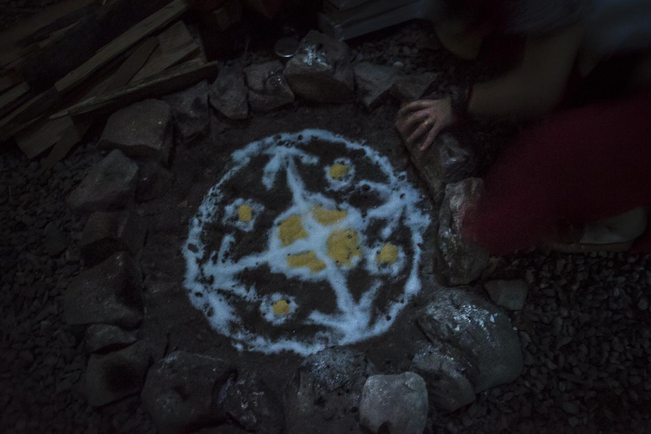 ITA  Polonia, Długopole Górne, maggio 2018.  Bea, che ama definirsi una strega, prepara una antica cerimonia di purificazione Maya. La strega compone con la mano sinistra un mandala sacro alla base del fuco. Rappresenta le cinque dimensioni, 4 legate agli elementi (terra, fuoco, aria, acqua), la quinta all'etere, che rappresenta il nuovo ciclo del mondo e la spiritualità.  I piccoli cerchi gialli sono gli occhi dei giaguari, che nella cosmogonia Maya hanno costruito il mondo. Al centro è rappresentata la terra, la sacralità. Il fuoco verrà acceso senza l'ausilio di carta, o di altri materiali.  ENG  Poland, Długopole Górne, May 2018 Bea, who likes to define herself a witch, is performing an ancient Mayan purification ceremony. With her left hand, the witch is making a sacred drawing at the base of the fire. She is opening the five dimensions, four of them are linked to the elements (earth, fire, air, water), while the fifth dimension is the ether, linked to the renewal and the new cycle of the world, to everything that is spiritual.  The small yellow circles represent the eyes of the jaguars. In the Mayan cosmogony, four jaguars built the world. At the center, the earth is represented, the holiness. The fire will be lit without the aid of paper or any other material.