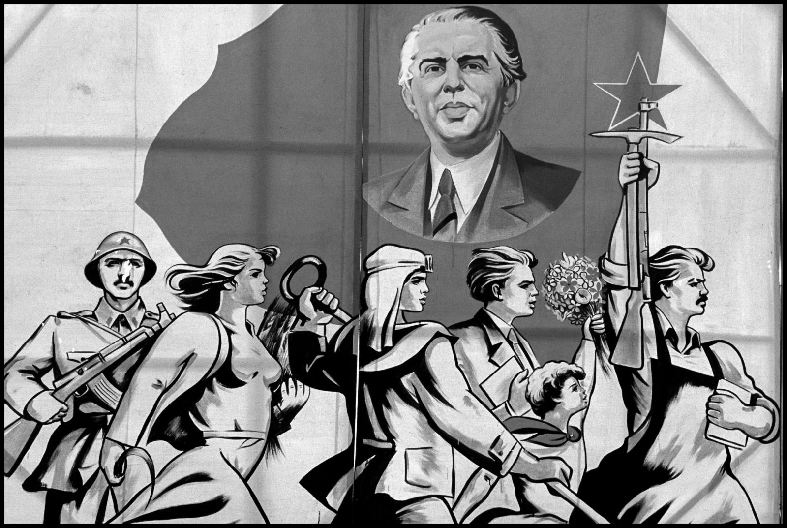 Albania 1989, il paese delle aquile, chiusa al mondo occidentale per quarantacinque anni fino alla caduta ufficiale del regime comunista nel febbraio del 1991.  Un cartellone a Tirana inneggiante a Enver Hoxha  e al Partito Comunista