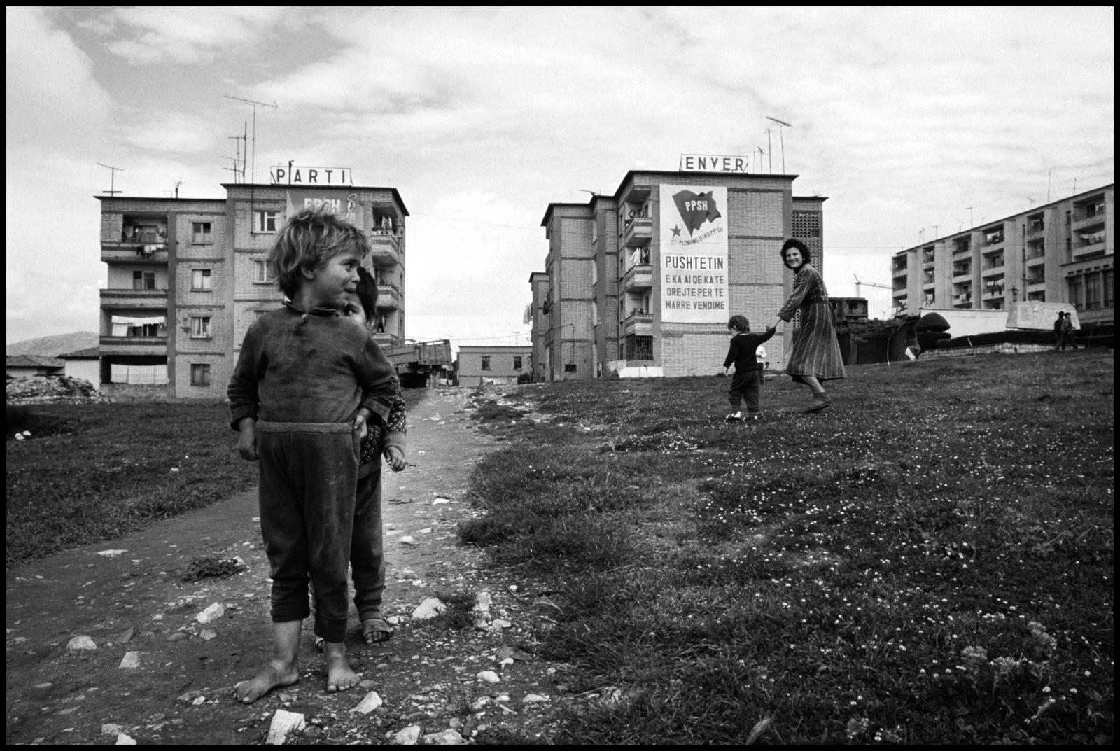 Albania 1989, il paese delle aquile, chiusa al mondo occidentale per quarantacinque anni fino alla caduta ufficiale del regime comunista nel febbraio del 1991. Edilizia popolare  alla periferia di Tirana con cartelloni inneggianti al Partito Comunista albanese