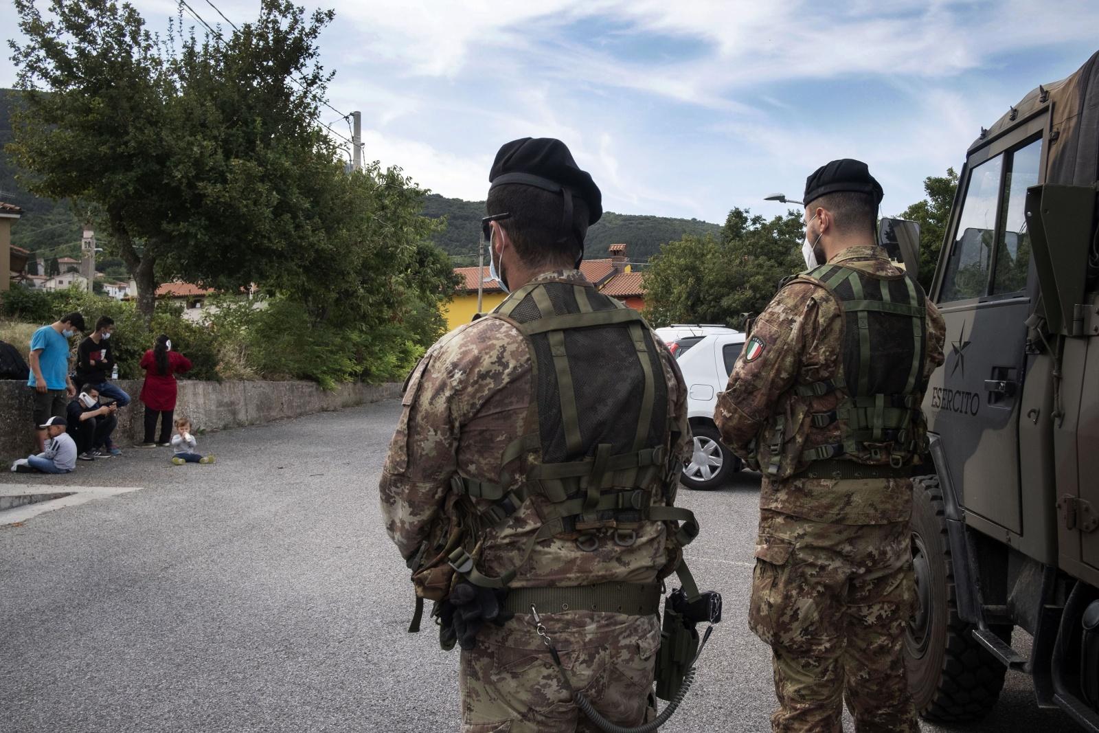 """Una famiglia di migranti afgani  con tre bambini piccoli dopo aver attraversato di notte i boschi nella zona carsica  di San Dorligo della Valle per arrivare nella città  di Dolina, vengono fermati da una pattuglia dell'Esercito di """"Strade Sicure"""" per essere identificati."""