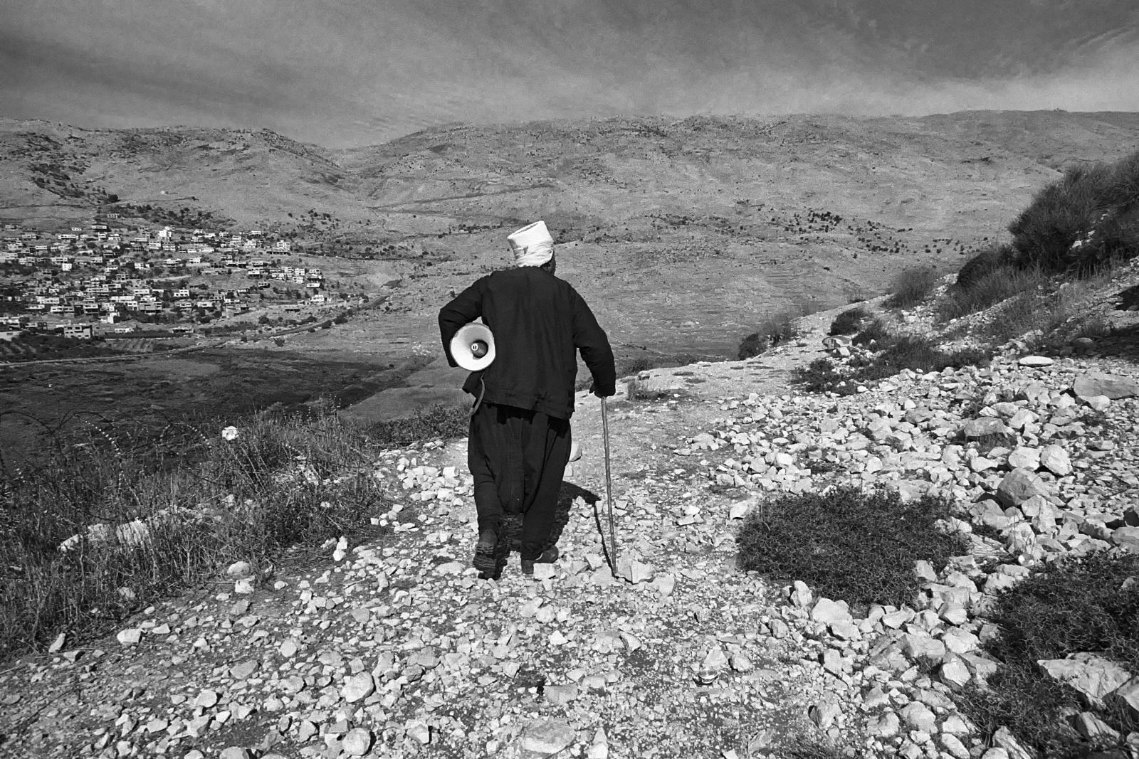 """Siria, Alture del Golan, """"Shouting valley"""" la valle delle urla. Il capo famiglia druso si allontana dopo aver parlato con i suoi parenti che vivono  dall'altra parte della valle in territorio israeliano"""