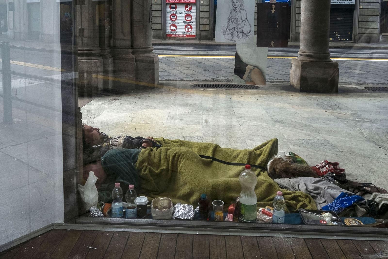 Senzatetto dormono nel freddo dell'inverno sotto i portici nel salotto torinese